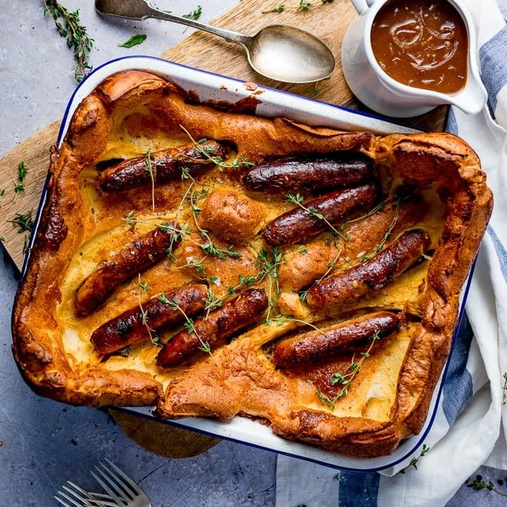 Overhead of toad in the hole on light background with jug of gravy