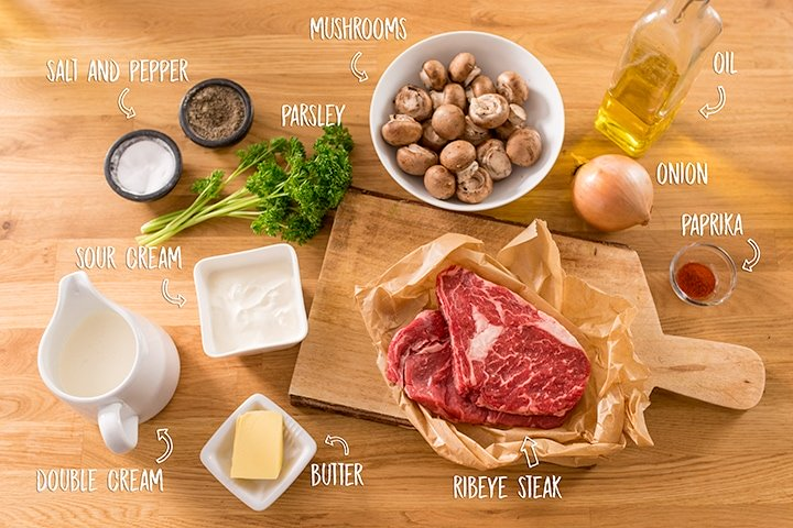 Ingredients for beef stroganoff on a wooden background