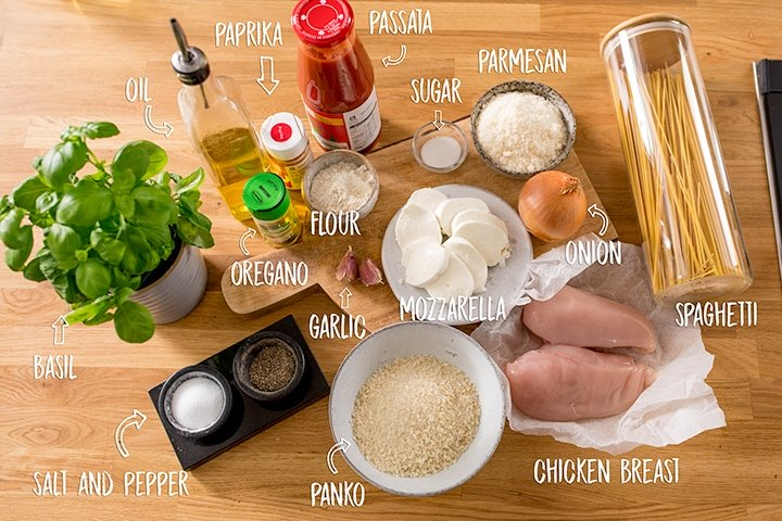 Ingredients for chicken parmesan on a wooden background
