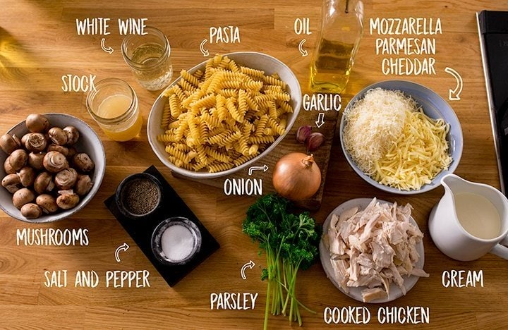 Ingredients for chicken alfredo pasta bake on a wooden table