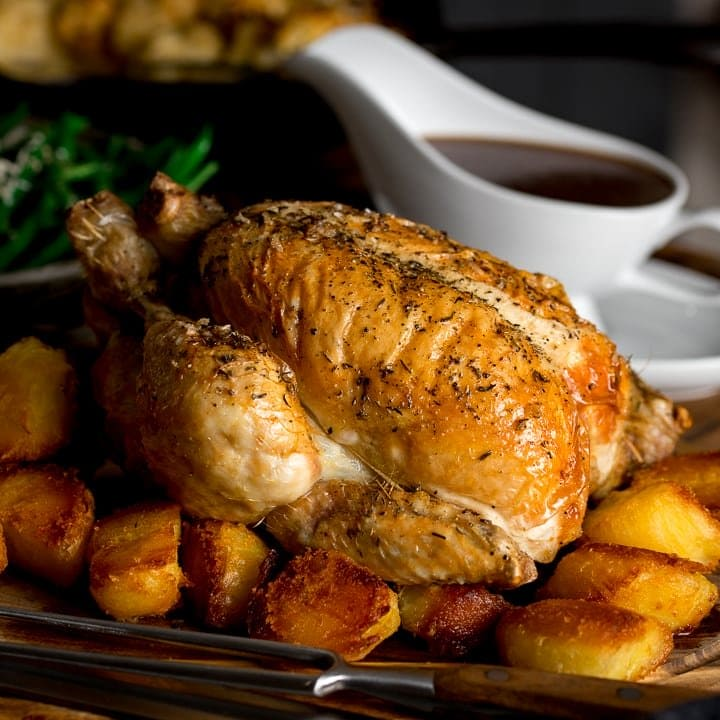 roast chicken on a board with potatoes and gravy