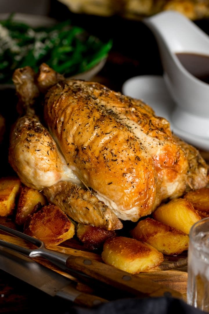 roast chicken on a board with roast potatoes
