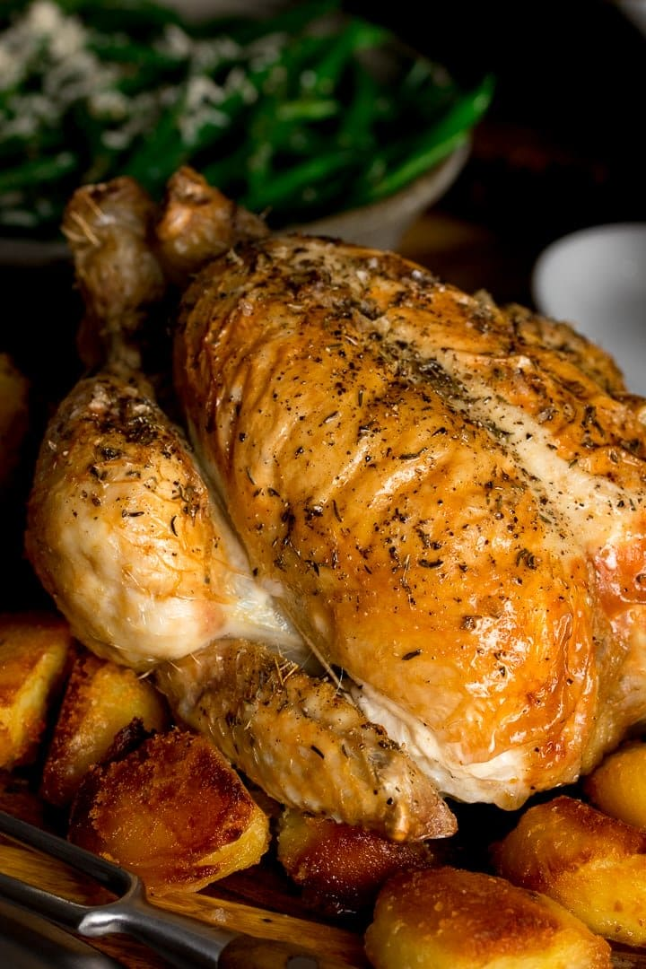 Close up of roast chicken on a board with potatoes
