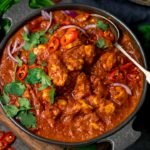 chicken madras in a serving bowl topped with chilles and coriander