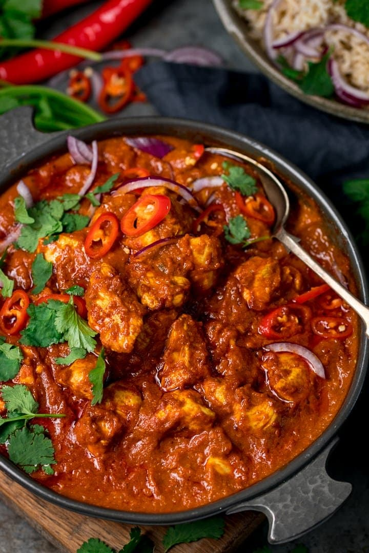 chicken madras in a dark serving bowl with a spoon in the bowl