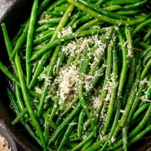 green beans sprinkled with parmesan in a pan