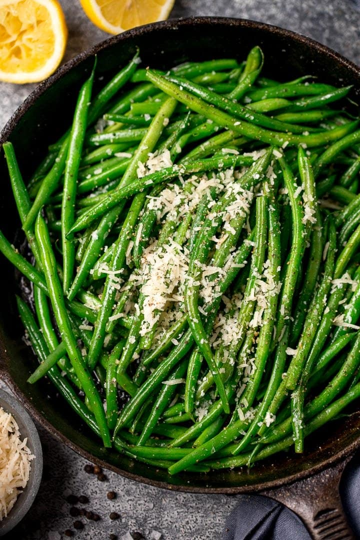 green beans in a pan with parmesan and lemon