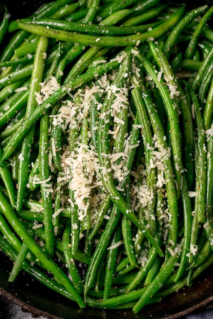 Close up of green beans in a pan with parmesan on top