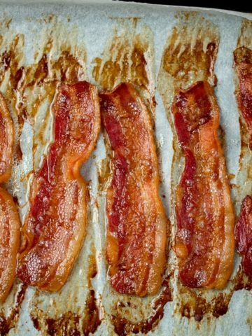 Square image of strips of cooked bacon on a tray