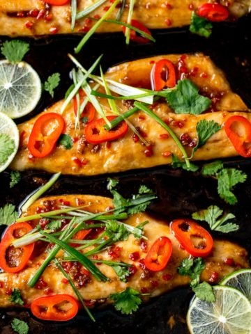 Asian-style sea bass fillets on a baking tray with spring onions and chillies