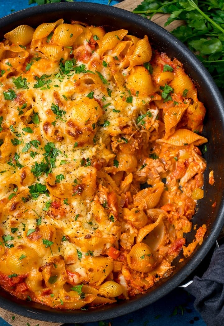 tuna tomato pasta bake in a dark pan topped with parsley