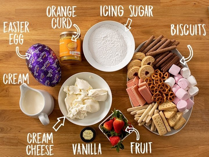 Ingredients for making Creme Egg Cheesecake Dip on a wooden table