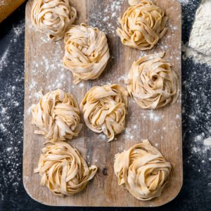 Little piles of homemade pasta on a wooden board