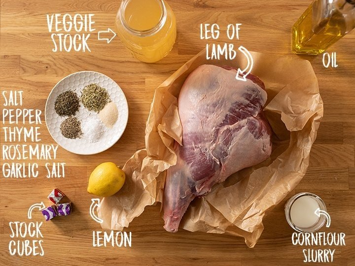 Ingredients for roast leg of lamb with gravy on a wooden table