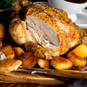 Sliced roast chicken on a board with potatoes and gravy.