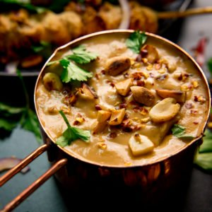 Satay sauce in a small copper pan topped with peanuts and coriander