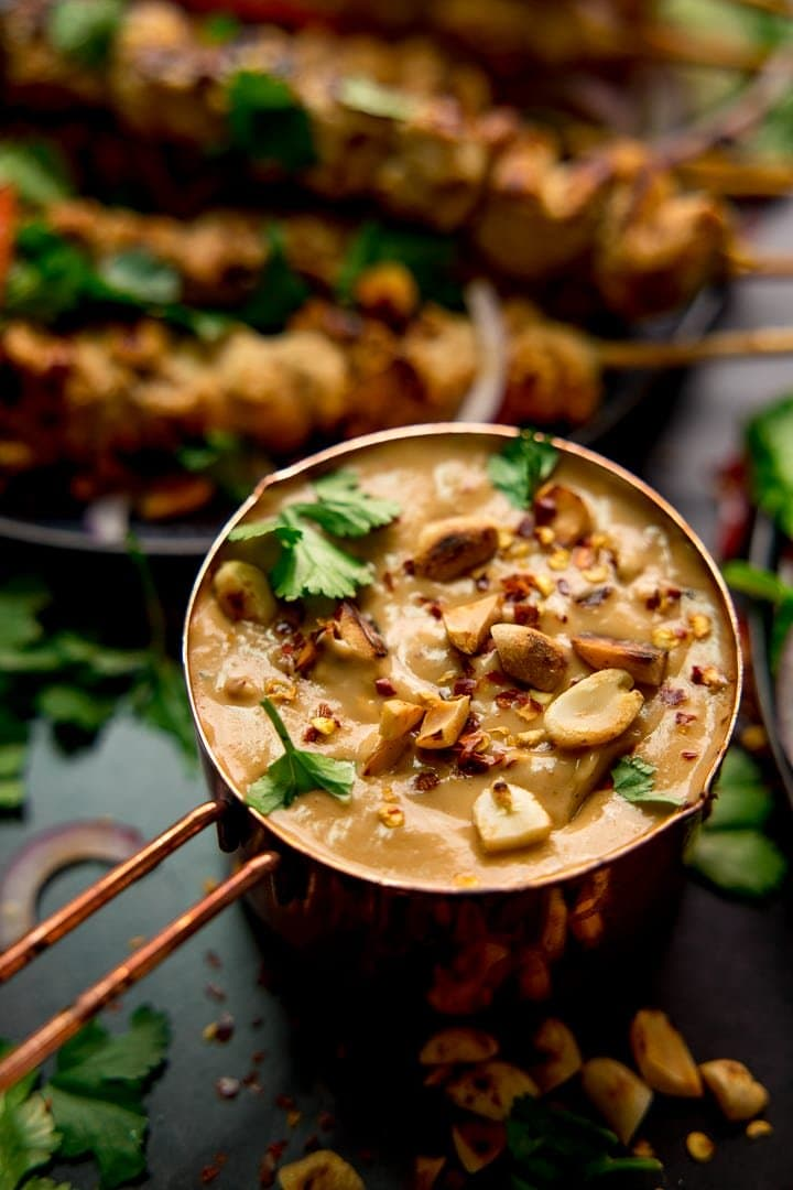 Satay sauce in a small copper pan topped with peanuts and coriander. Chicken skewers in the background
