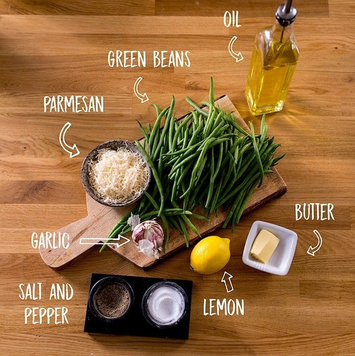 Ingredients for garlic green beans with parmesan on a wooden table