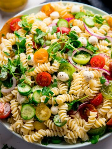 Large bowl filled with pasta salad on a light background