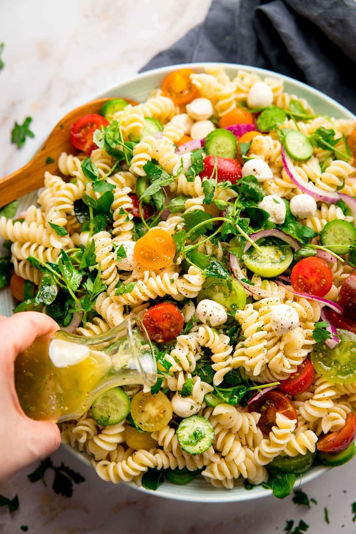Italian dressing being poured onto a bowl of pasta salad