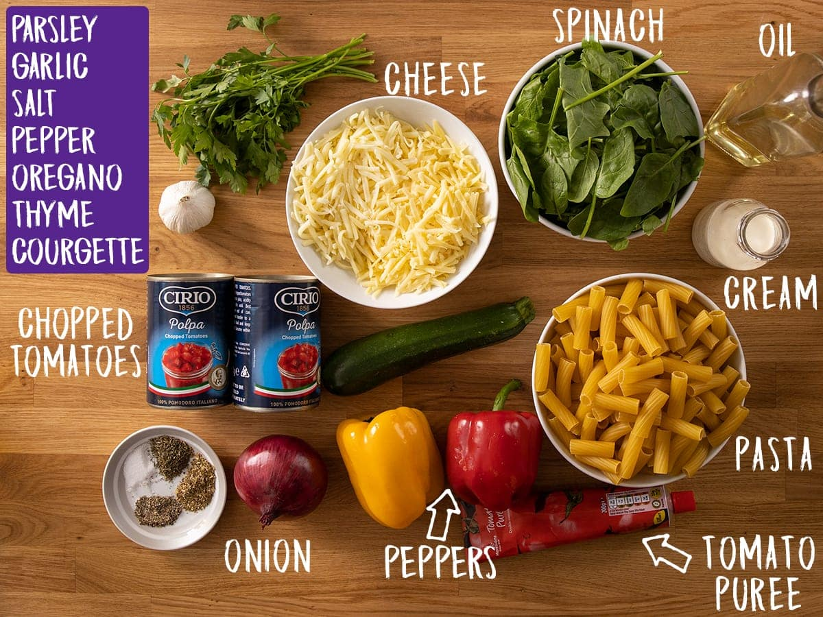Ingredients for vegetable pasta bake on a wooden table
