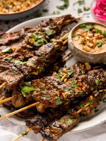 beef satay on wooden skewers on a white plate