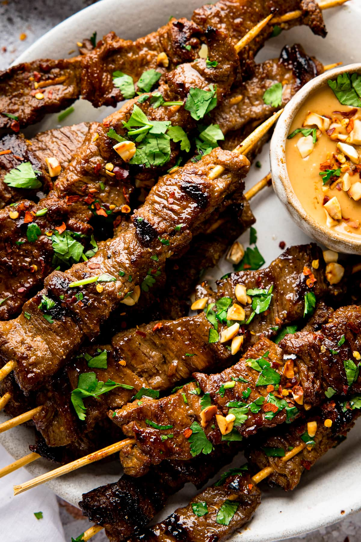 Close up of beef satay skewers on a plate, topped with coriander and peanuts