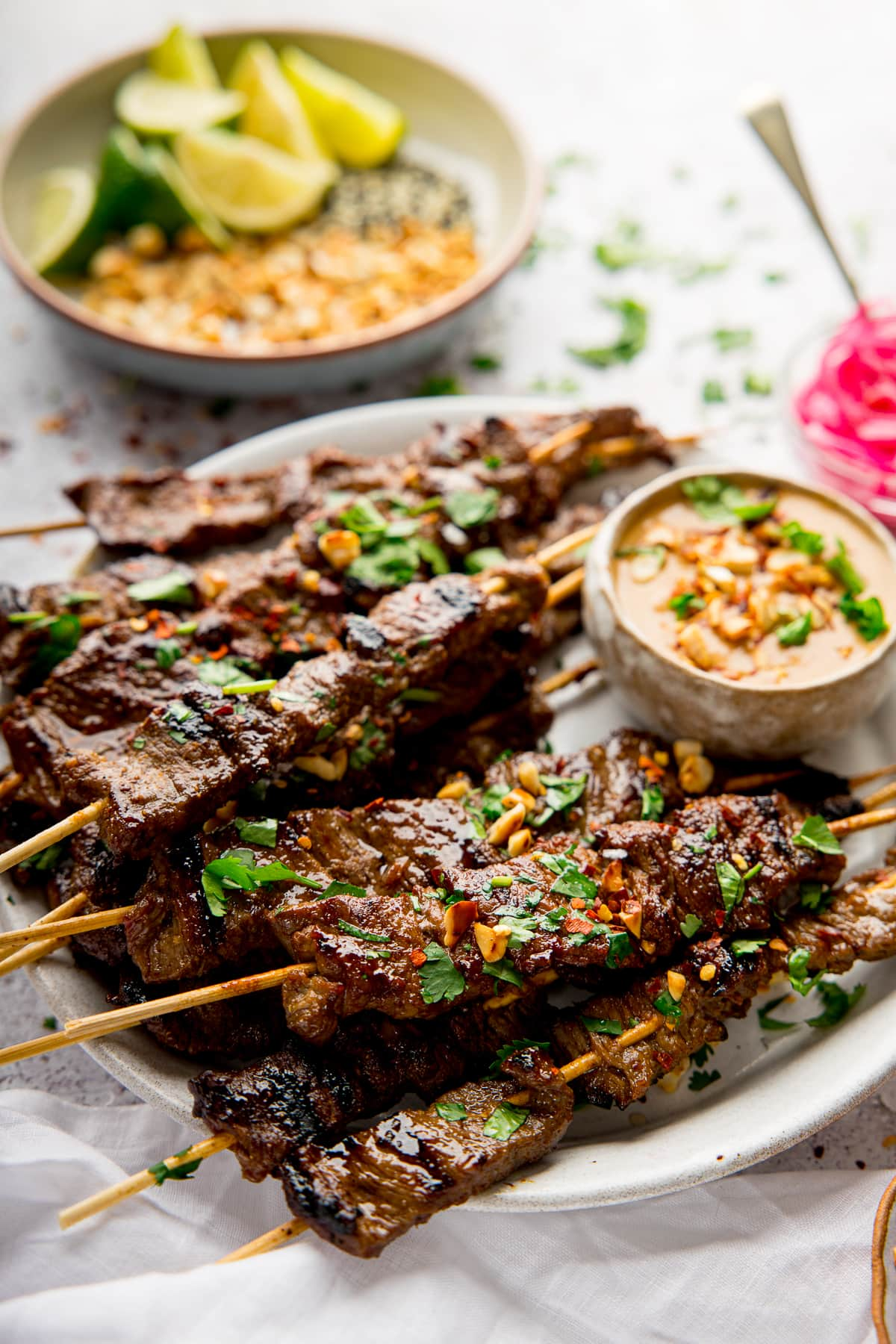 beef satay on a white plate with satay sauce. Bowl of chopped peanuts and lime in background.