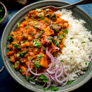 chickpea and sweet potato curry in a bowl with rice and red onion