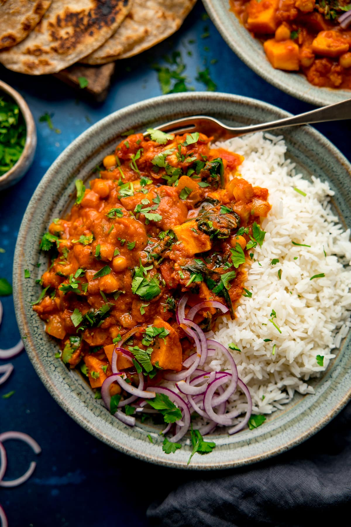chickpea and sweet potato curry with rice in a green bowl