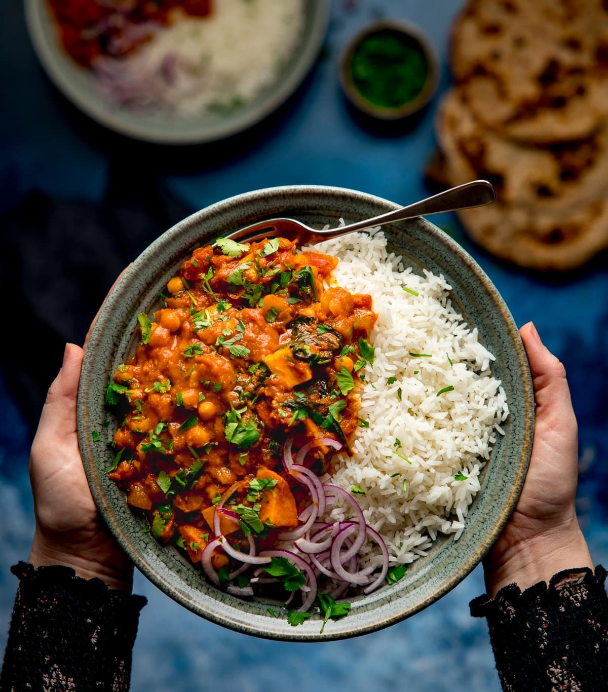 Bowl of chickpea and sweet potato curry with rice being held by two hands