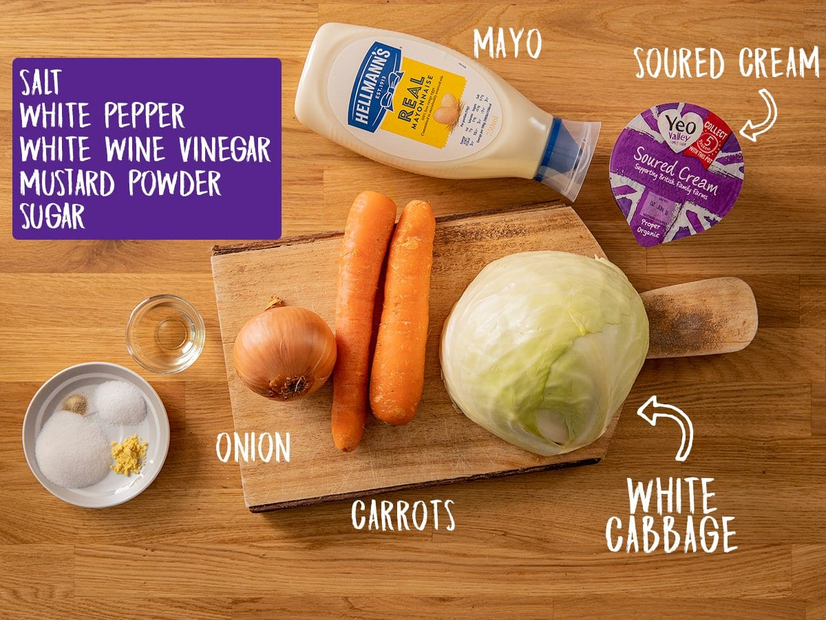 Ingredients for making creamy coleslaw in a wooden table