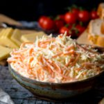 creamy coleslaw in a bowl. Cheese and cherry tomatoes in the background