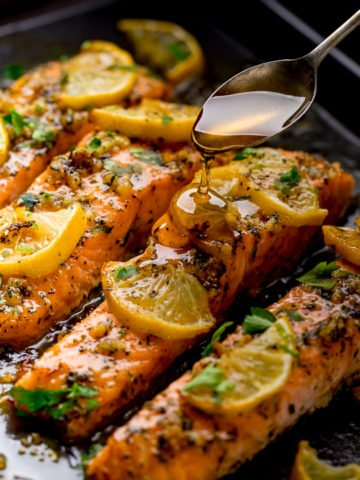 Baked salmon on a tray topped with lemon slices. Honey being drizzled on top with a spoon.