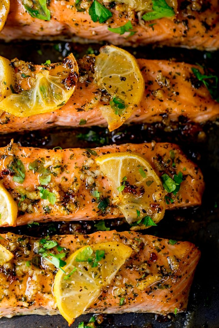 4 fillets of honey garlic baked salmon on a tray topped with lemon slices and herbs