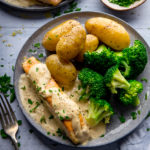 Salmon on a grey plate with creamy white wine sauce, broccoli and new potatoes