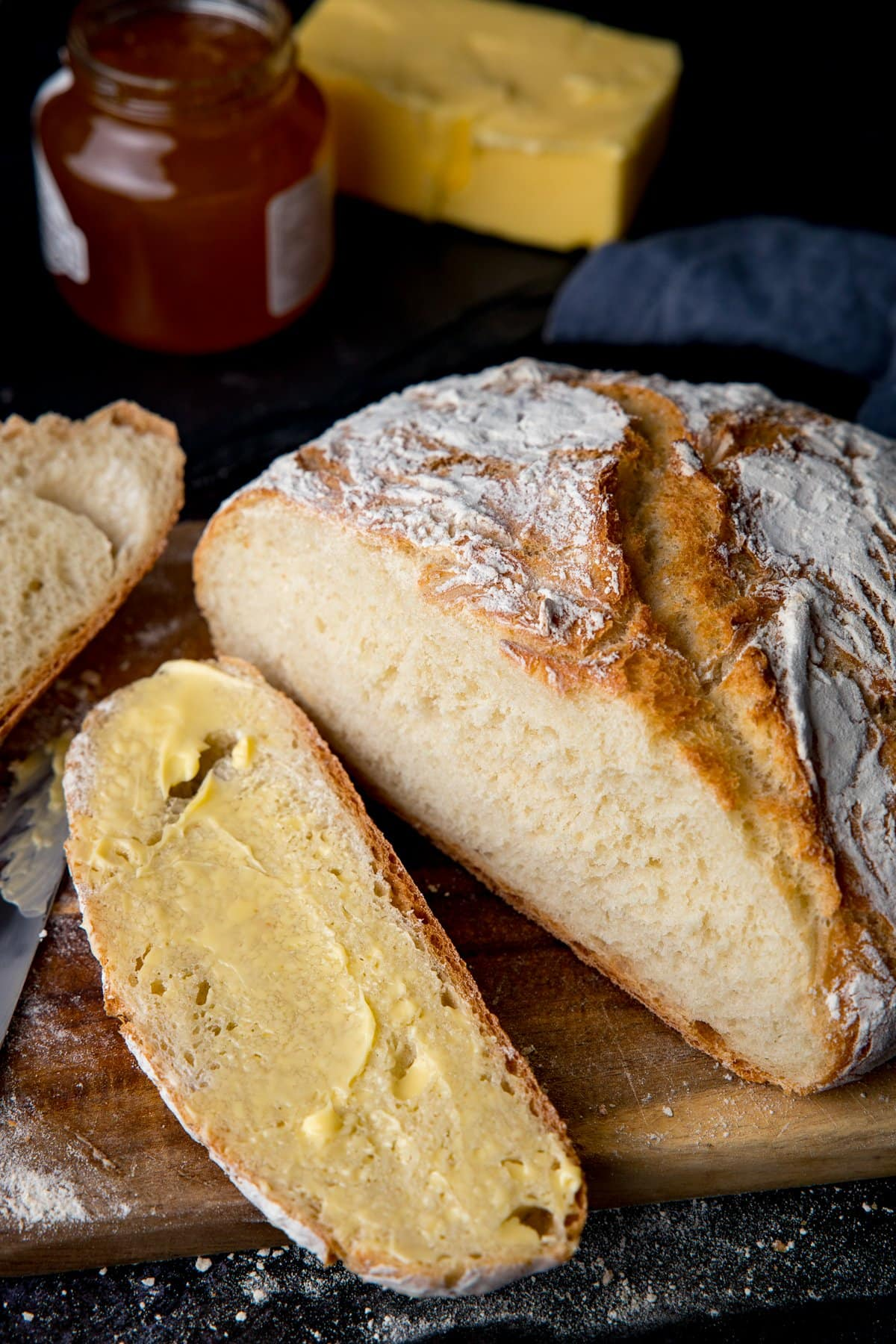 Homemade artisan bread slice open and slice spread with butter