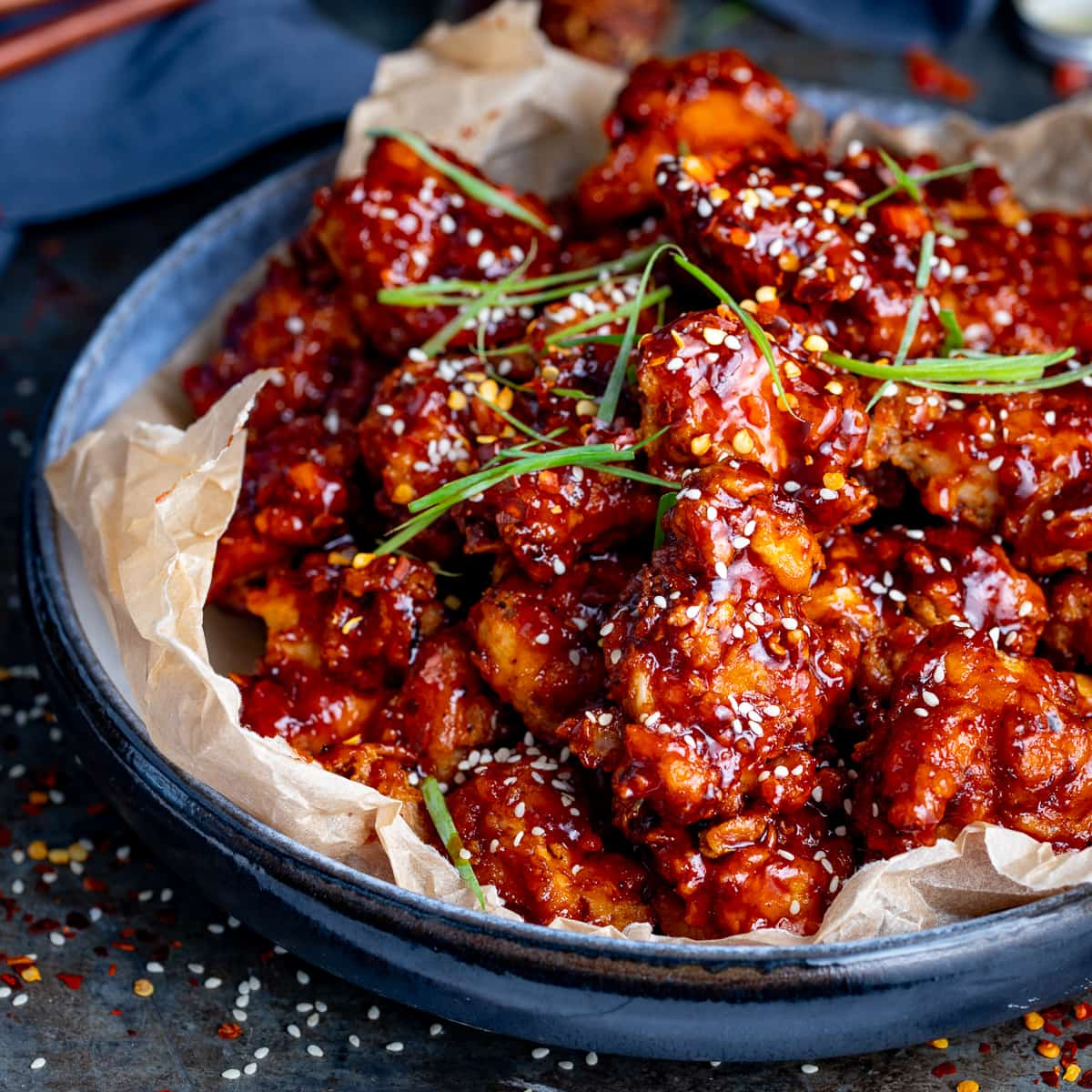Crispy Korean chicken in a blue bowl topped with strips of spring onion
