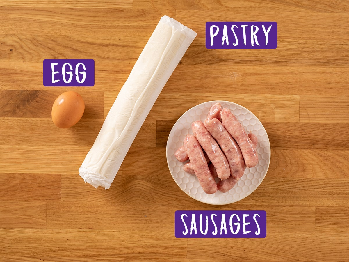 Ingredients for sausage rolls on a wooden board