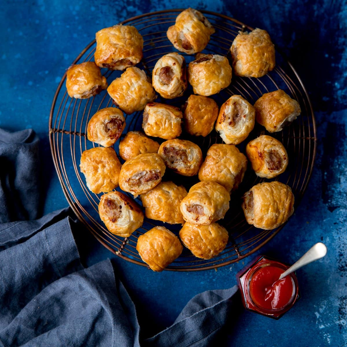 Square image of sausage rolls on a cooling rack on a dark blue background