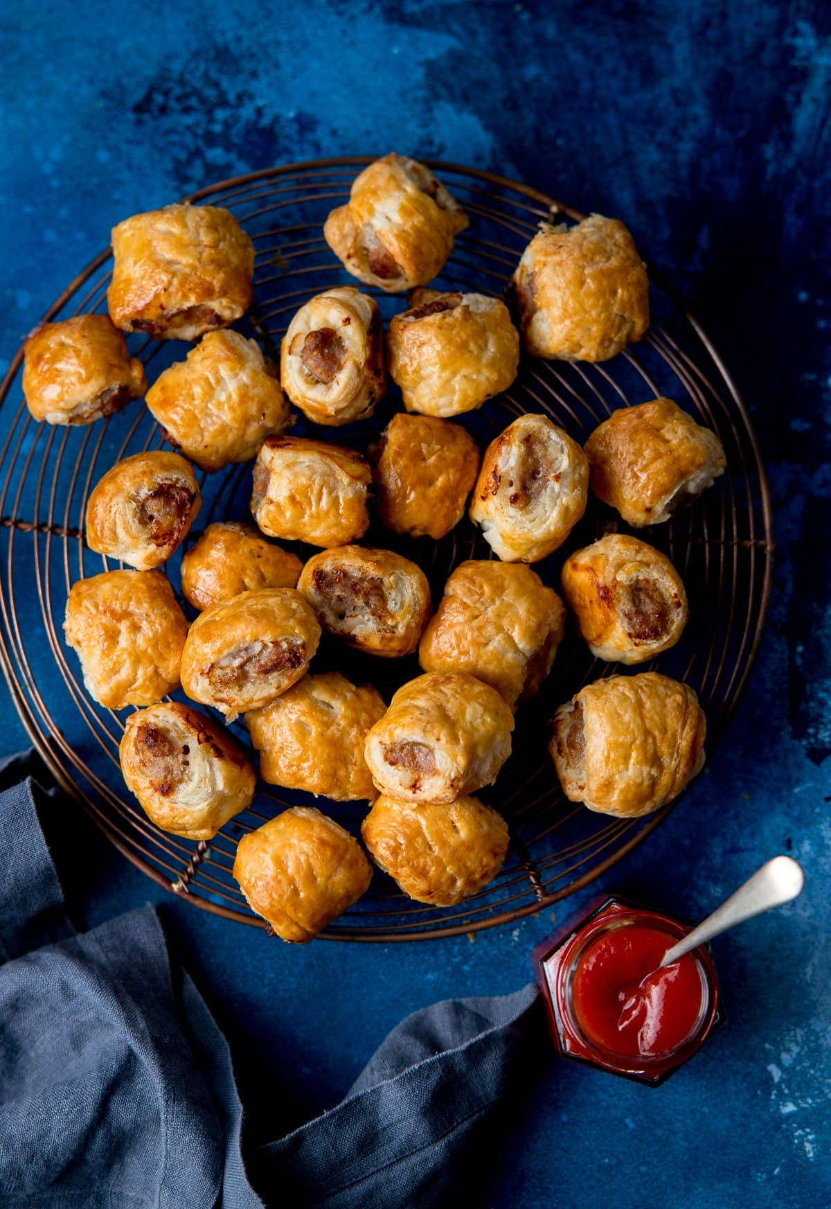 sausage rolls on a cooling rack on a dark blue background with a pot of ketchup