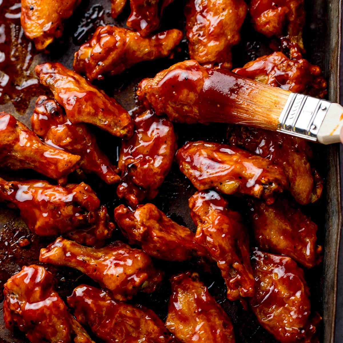 BBQ chicken wings on a tray with BBQ sauce being brushed on