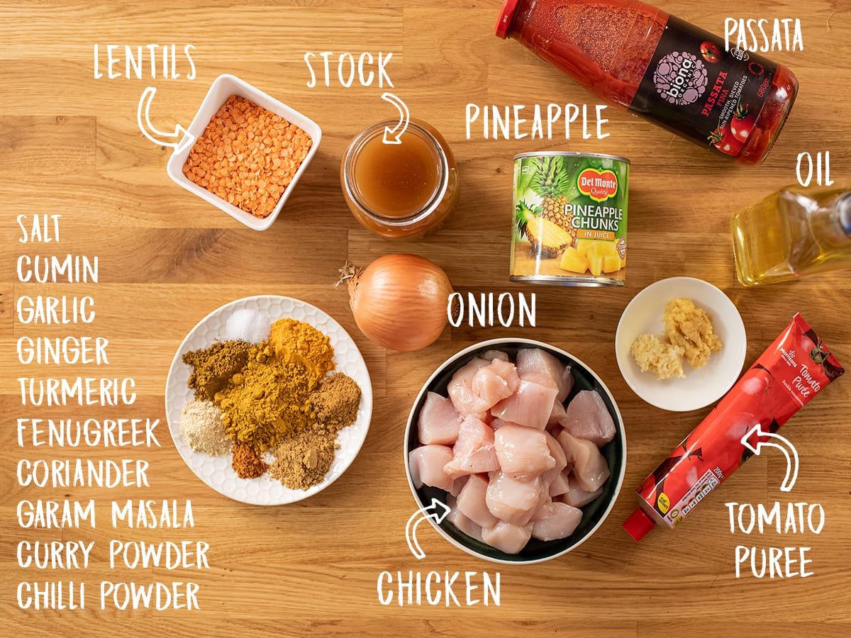 Ingredients for chicken dhansak on a wooden table