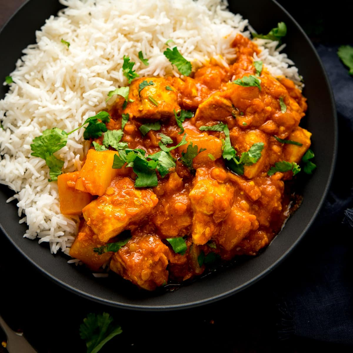 chicken dhansak with rice in a black bowl