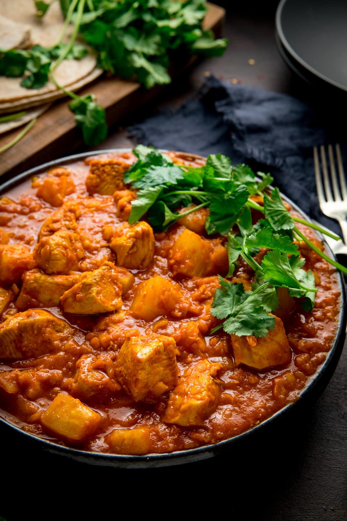 chicken dhansak in a bowl with coriander on top