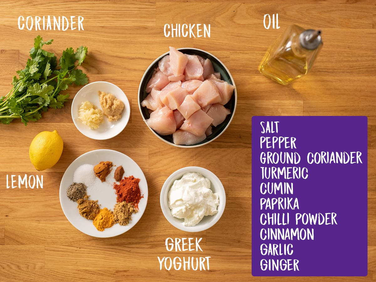 Ingredients for chicken tikka skewers on a wooden board