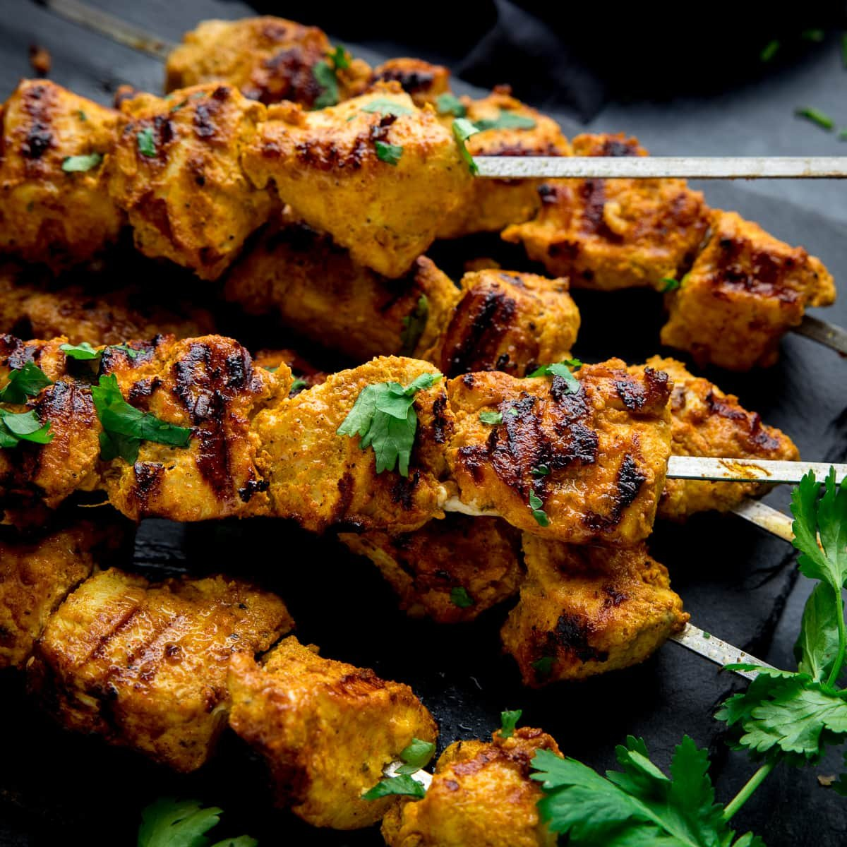 chicken tikka skewers on a dark background