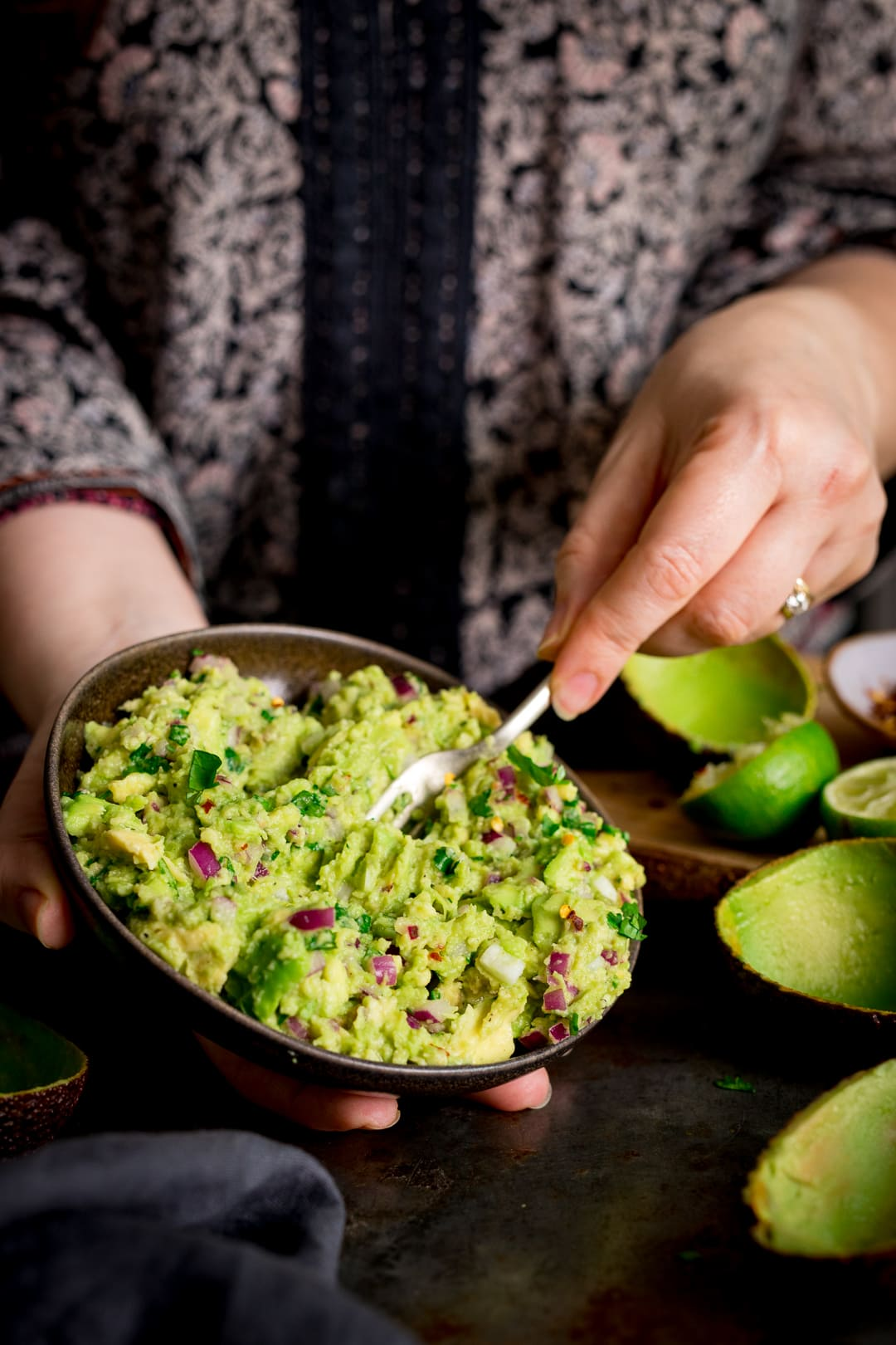Close up of hands stirring together guacamole in a bowl..