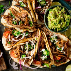 Square image of a plate of Lamb Barbacoa Carnita Tacos with a bowl of guacamole