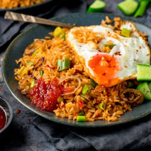 nasi goreng rice on a plate, topped with a fried egg and sweet chilli sauce